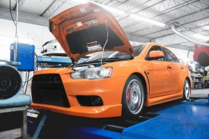 Orange EVO X with body kit getting tuned on Mustang AWD 4WD Dyno Dynamometer