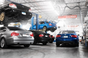 Shop with cars on lifts, three BMW's and two subaru STi