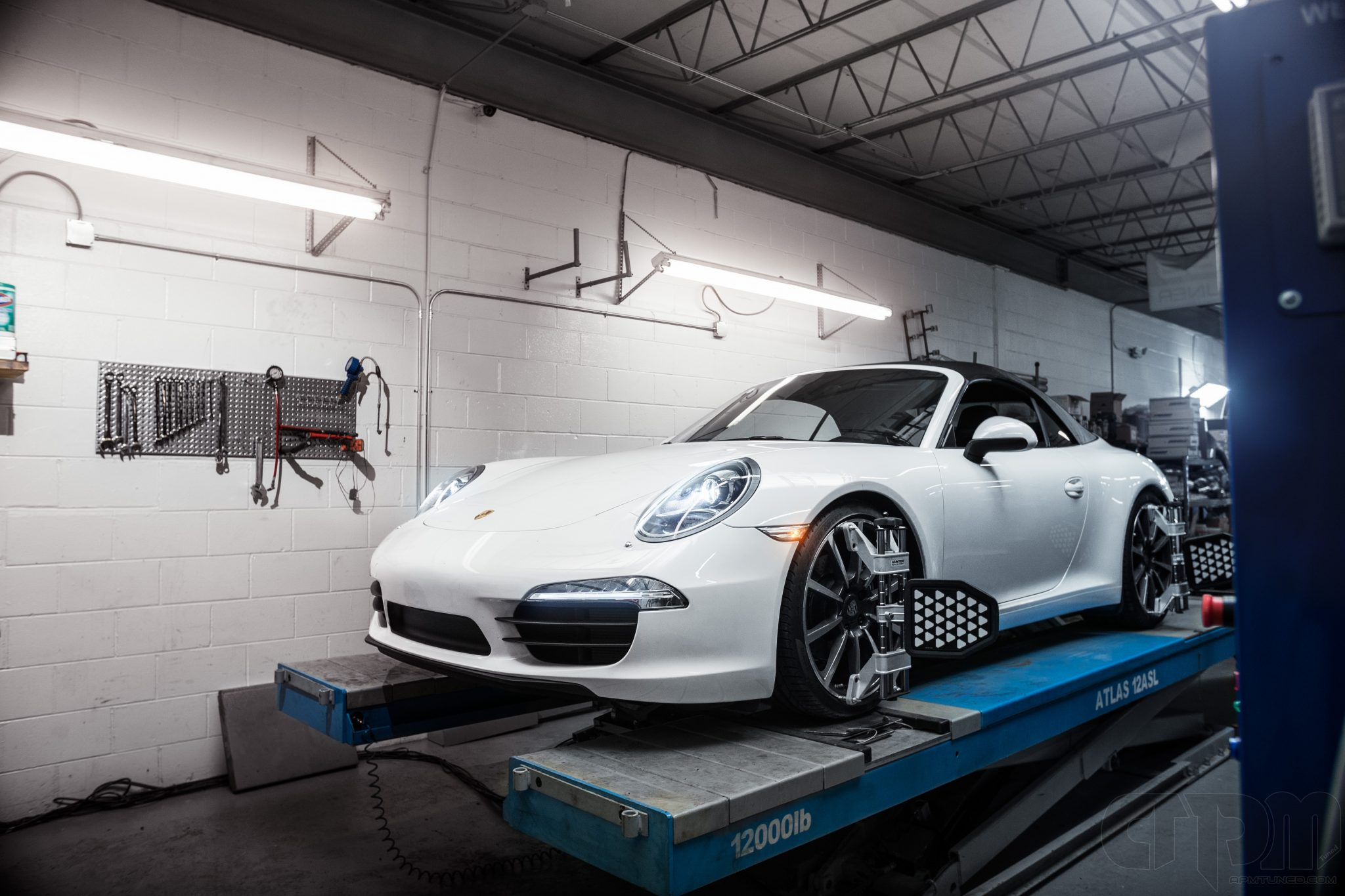 White Porsche convertible getting an alignment on our rack