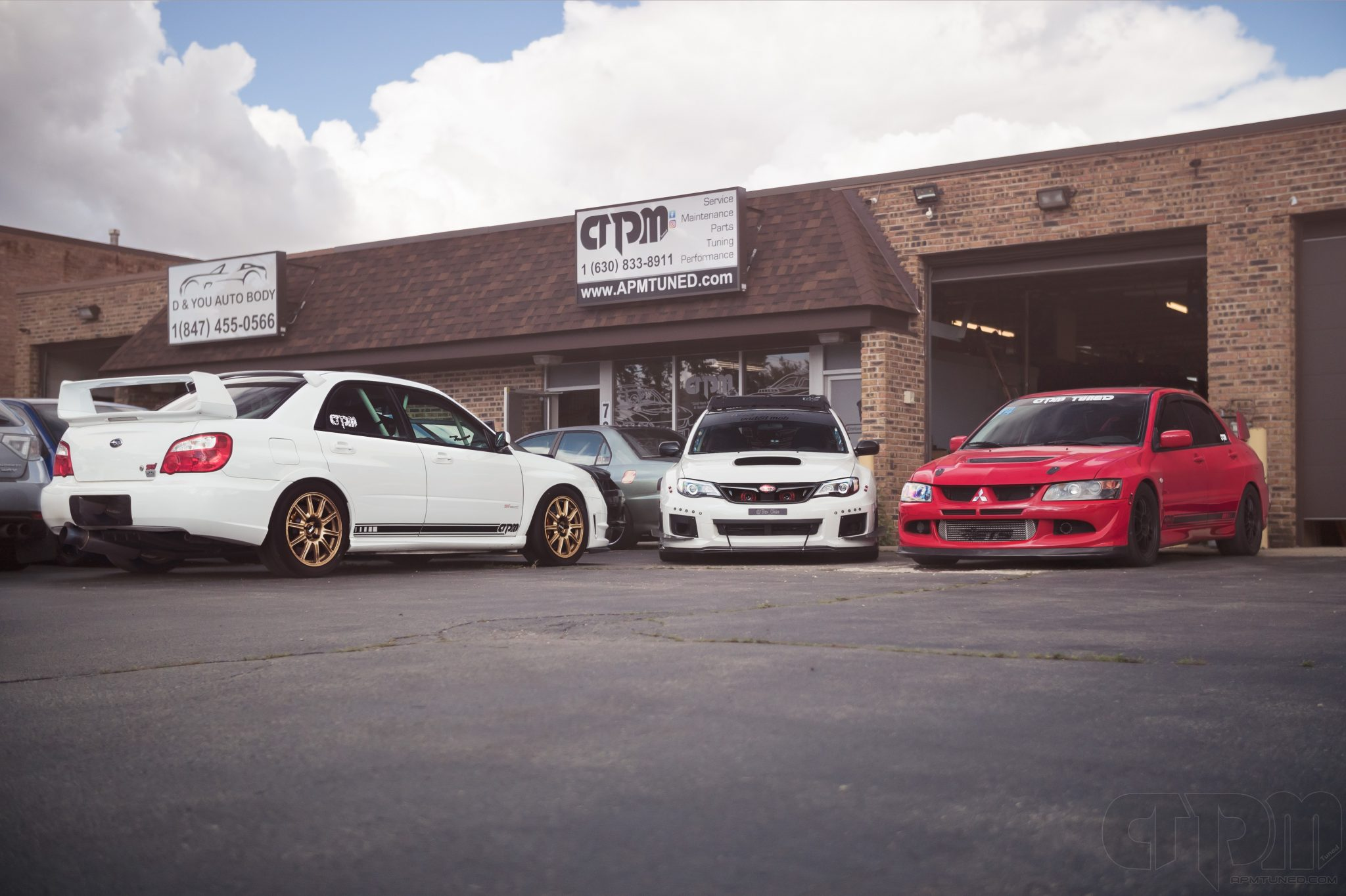 Our White Sponsored Subaru STi, White WRX Hatchback, and Shop Car Red EVO parked together infront of our Villa Park location
