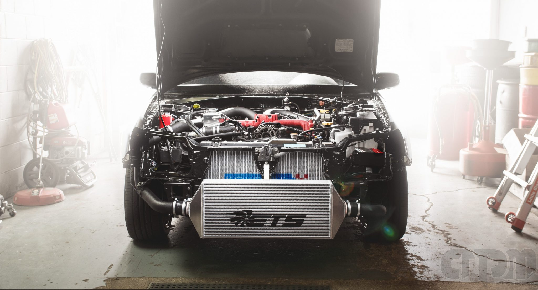 Front shot of Black STi with ETS intercooler and custom piping against backlight